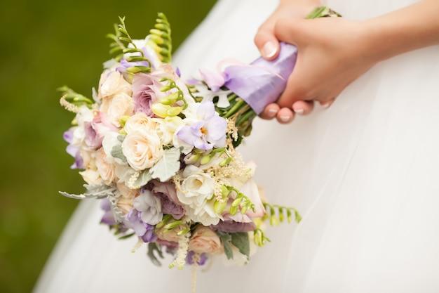 Schöner hochzeitsblumenstrauß in den händen der braut