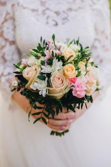 Schöner hochzeitsblumenstrauß mit gelben rosen, weißen chrysanthemen und rosa alstroemeria in den händen