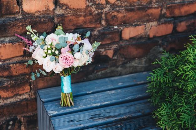 Schöner hochzeitsblumenstrauß von rosen steht auf holzbank gegen backsteinmauerhintergrund