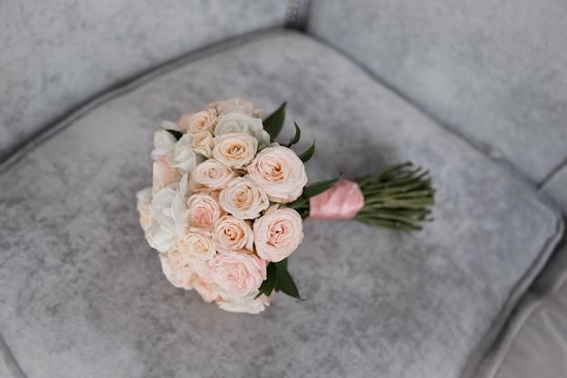 Schöner hochzeitsbrautstrauß von rosen auf dem sofa