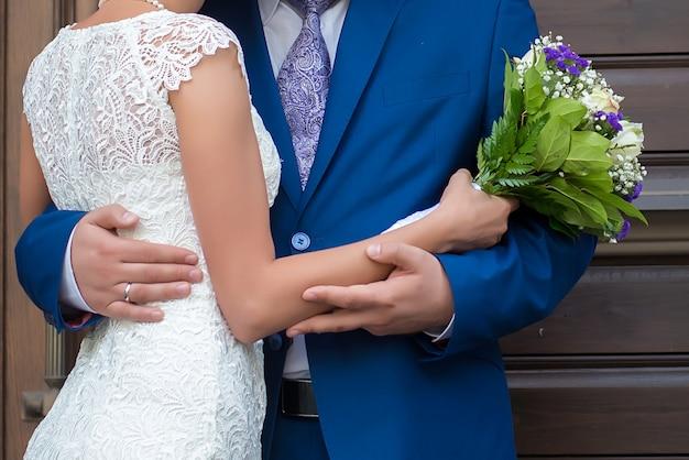 Schöner hochzeitsstrauß in den händen der braut und des bräutigams schließen oben