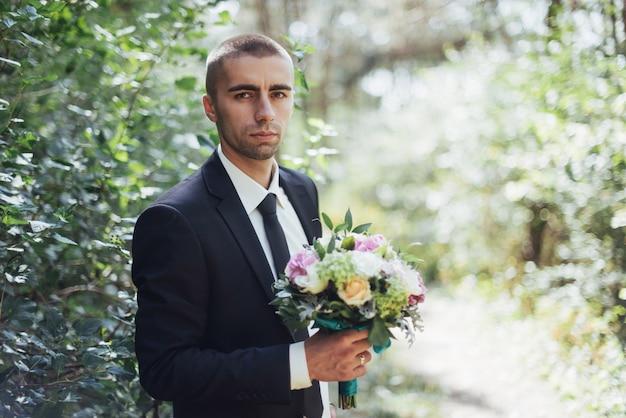 Schöner hochzeitsstrauß in den händen des bräutigams
