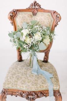Schöner hochzeitsstrauß mit weißen rosen, kiefer und eukalyptus, die auf dem weinlesestuhl liegen