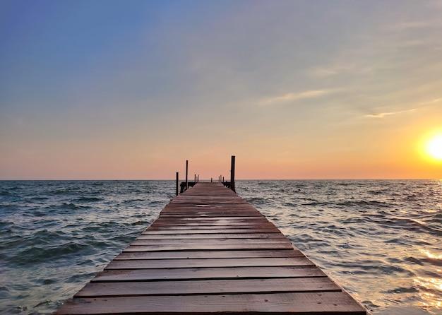 Schöner hölzerner angelpier bei sonnenuntergang auf dem meer