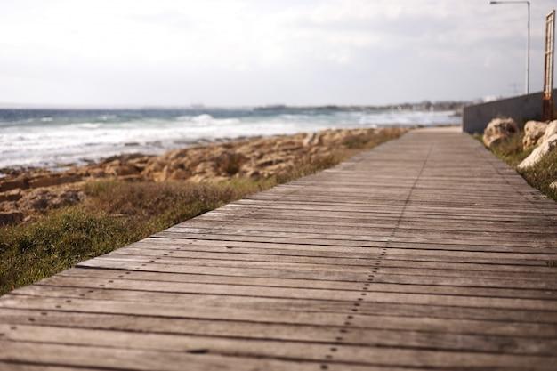 Schöner hölzerner fußgängerweg entlang der küste. der fußweg ist mit vintage-brettern gepflastert. naturholzbretter am strand.