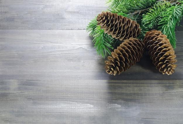 Schöner hölzerner hintergrund mit weihnachtskiefernkegeln im oberen recht
