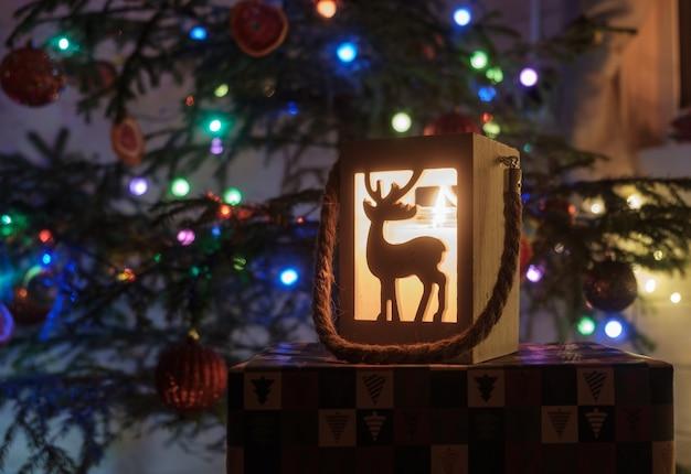 Schöner hölzerner kerzenhalter mit hirsch und weinleselampe unter weihnachtsbaum. elemente der weihnachtsdekoration