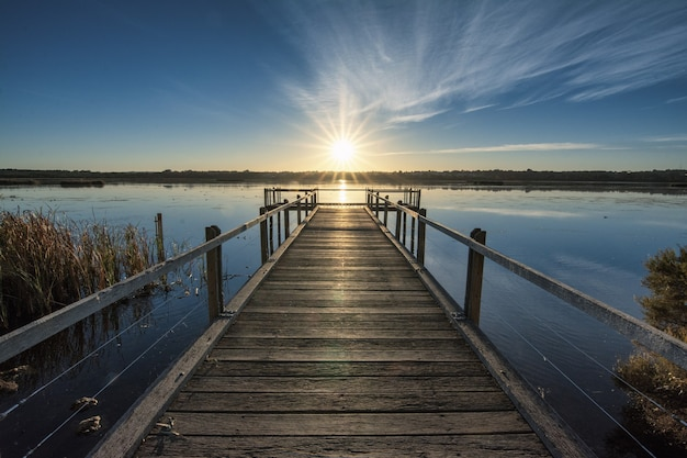 Schöner hölzerner pier am ruhigen ozean mit dem schönen sonnenuntergang über dem horizont