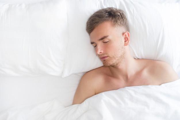 Schöner hübscher bärtiger kerl, junger mann, mann, der im bett liegt, schlafzimmer zu hause, allein schlafend auf seinem rücken auf weißem kissen bedeckt mit decke. gesundes schlafkonzept. draufsicht, kopierraum