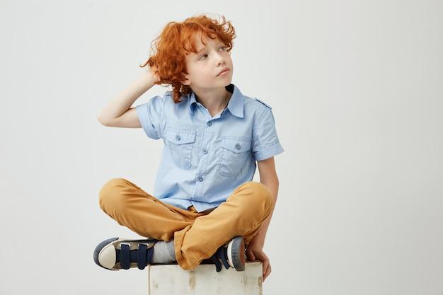 Schöner ingwerjunge mit lockigem haar und sommersprossen in der freizeitkleidung, die hand auf kopf hält und mit entspanntem ausdruck beiseite schaut.