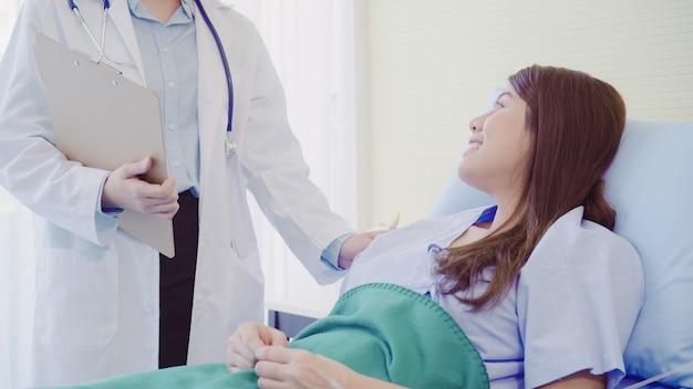 Schöner intelligenter asiatischer doktor und patient, die etwas mit klemmbrett bespricht und erklärt