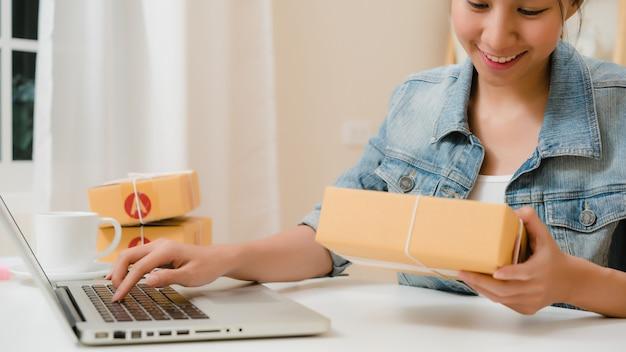 Schöner intelligenter asiatischer jungunternehmergeschäftsfrauinhaber von kmu, das produkt auf lager online überprüft und zum computer speichert, der zu hause arbeitet.