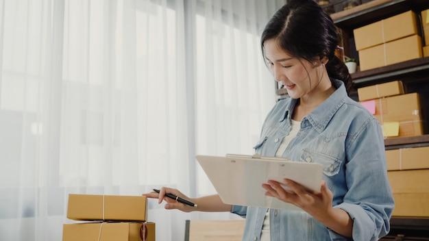 Schöner intelligenter asiatischer jungunternehmergeschäftsfrauinhaber von kmu produkt auf lager überprüfend