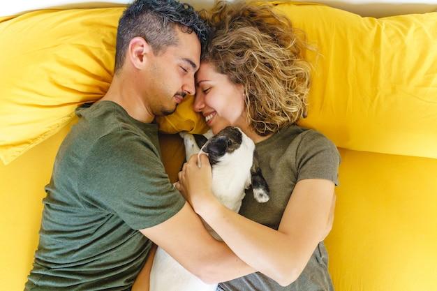 Schöner intimer moment eines paares mit haustier auf dem bett. horizontale draufsicht, die den hund drinnen umarmt.