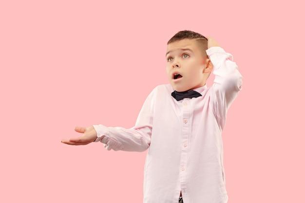 Schöner jugendlich junge, der überrascht und verwirrt lokalisiert auf rosa schaut
