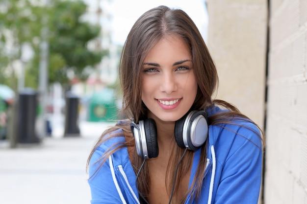 Schöner jugendlicher, der draußen mit kopfhörern sitzt