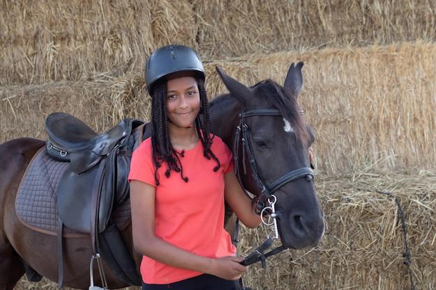 Schöner jugendlicher mit seinem pferd lernend zu reiten
