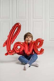 Schöner junge, der einen roten ballon auf einem weißen hintergrund sitzt und hält