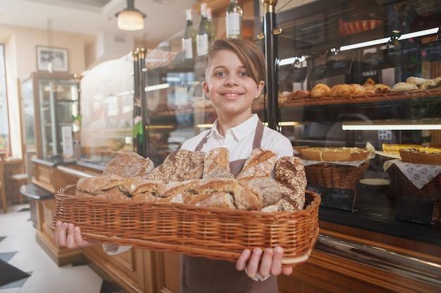 Schöner junge, der freudig lächelt, brotkessel trägt und in seiner familienbäckerei arbeitet