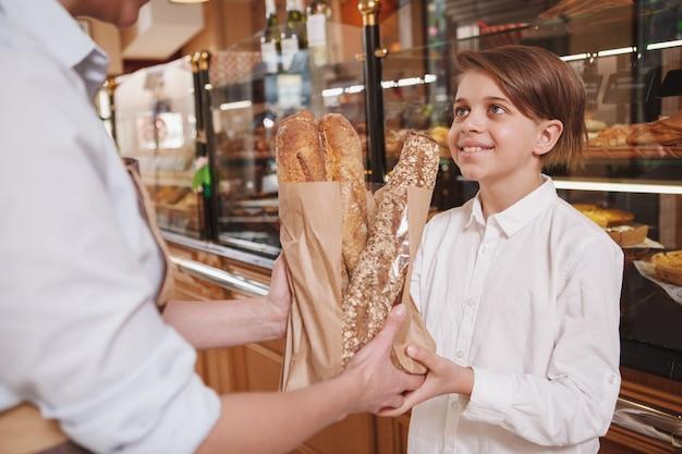 Schöner junge, der freudig lächelt und frisches brot in der bäckerei kauft