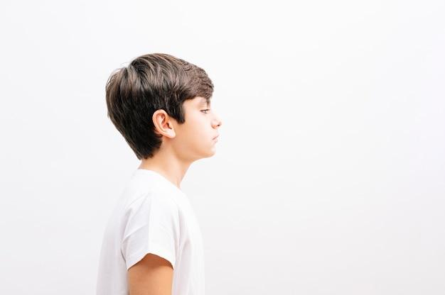 Schöner junge, der lässiges t-shirt trägt, das über lokalisiertem weißem hintergrund steht, der zur seite schaut, profilprofilhaltung mit natürlichem gesicht entspannen.