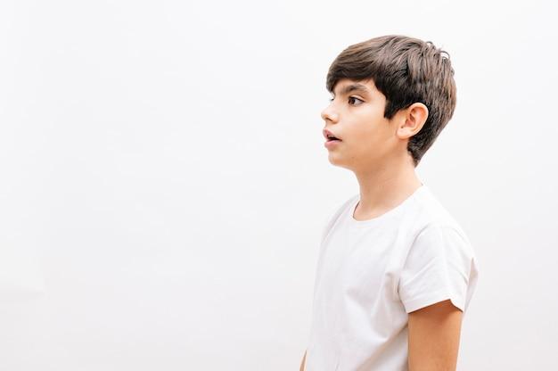 Schöner junge, der lässiges t-shirt trägt, das über lokalisiertem weißem hintergrund steht, der zur seite schaut.