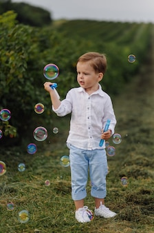 Schöner junge, der mit blasen am sonnigen tag im garten spielt.