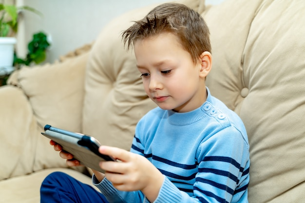 Schöner junge, der zu hause auf drahtloser tablette auf einem hellen sofa spielt.