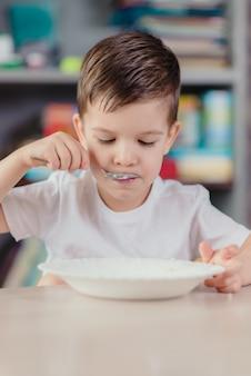 Schöner junge isst milchbrei. nettes baby, das frühstückt, zu hause sitzend an einem tisch in der küche.