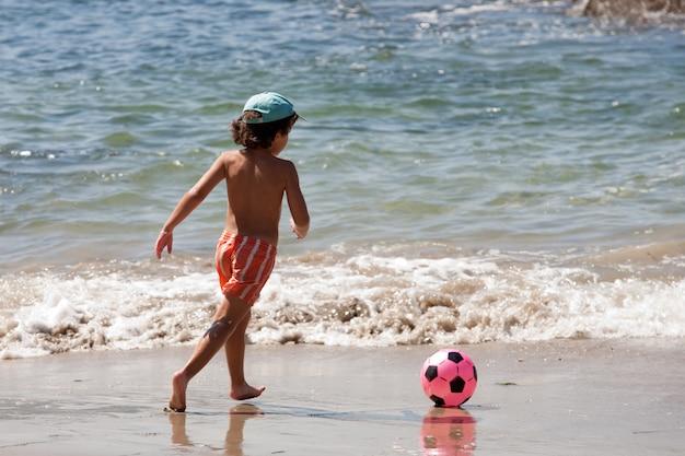 Schöner junge mit einem fußball, der im strand spielt