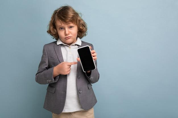 Schöner junge mit lockigem haar, der anzug hält, der das telefon einzeln auf blauem hintergrund hält und die kamera anschaut und das smartphone mit leerem bildschirm zeigt und auf den bildschirm zeigt. attrappe, lehrmodell, simulation
