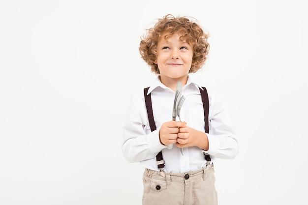 Schöner junge mit lockigem haar im weißen hemd, braunem hut, brille mit schwarzen hosenträgern hält ein messer und gabeln lokalisiert auf weißem hintergrund