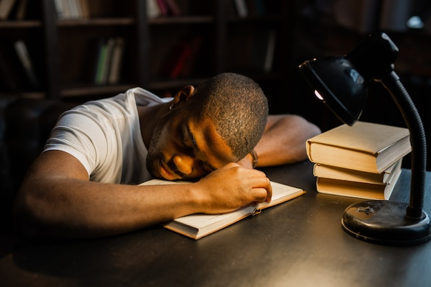 Schöner junger afrikanischer mann, der auf dem tisch mit büchern schläft