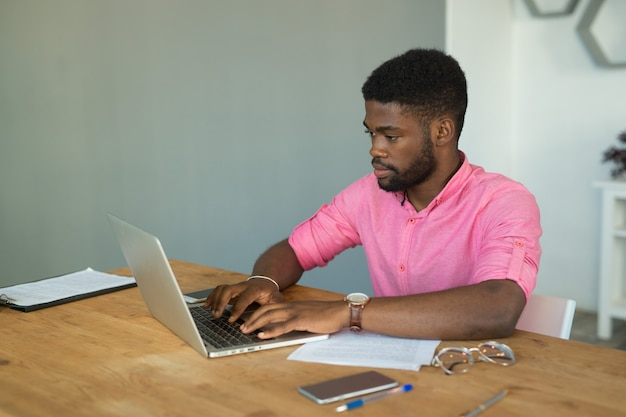 Schöner junger afrikanischer mann im büro am tisch mit laptop