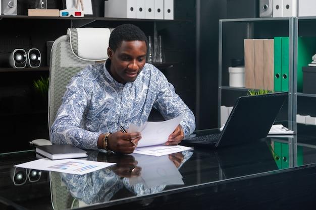 Schöner junger afroamerikanergeschäftsmann, der mit dokumenten und laptop im büro arbeitet