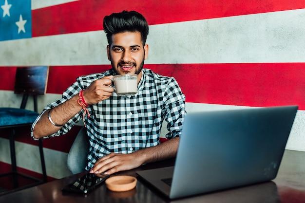 Schöner, junger amerikanischer geschäftsmann, freiberufler in freizeitkleidung in der bar, entspannend bei einer tasse kaffee.