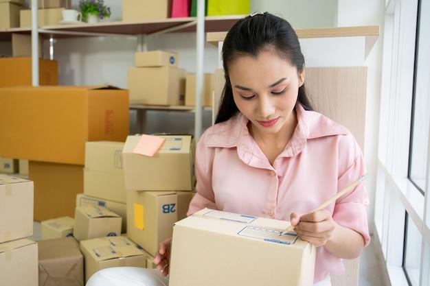 Schöner junger asiatinon-line-unternehmer, frau, die produkte durch on-line-marktplatz verkauft.
