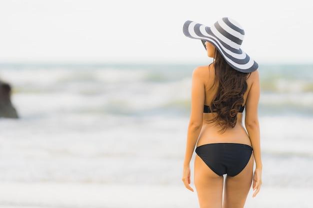 Schöner junger asiatischer frauenabnutzungsbikini des porträts auf dem strandseeozean