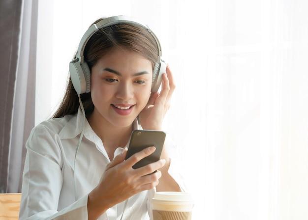 Schöner junger asiatischer frauengebrauch smartphone und hörende musik auf kopfhörer.