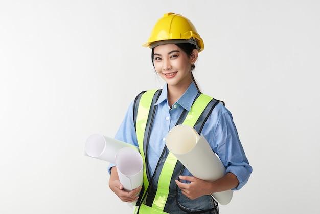 Schöner junger asiatischer fraueningenieur und gelber schutzhelm auf weißem hintergrund, baukonzept, ingenieur, industrie.