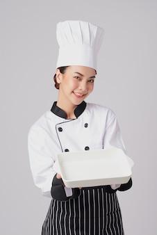 Schöner junger asiatischer frauenkoch, der leere weiße platte hält.