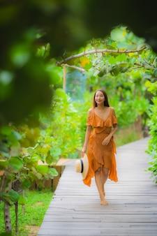 Schöner junger asiatischer frauenweg des porträts auf wegweg im garten