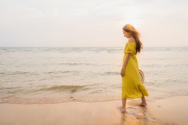 Schöner junger asiatischer frauenweg des portraits auf dem strand- und seeozean mit dem glücklichen lächeln entspannen sich