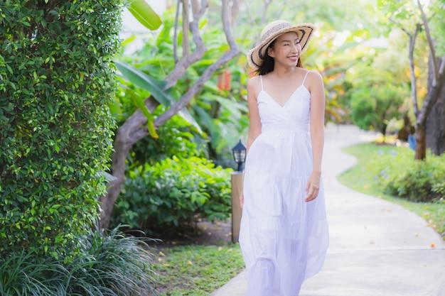Schöner junger asiatischer frauenweg des portraits mit dem glücklichen lächeln und entspannen sich im park