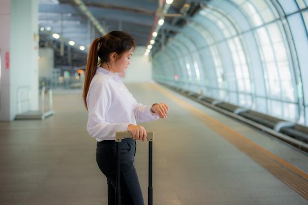 Schöner junger asiatischer geschäftsfraureisender, der in der hand uhr mit gepäck, wartezug bahnstation, reise und ferien betrachtet.