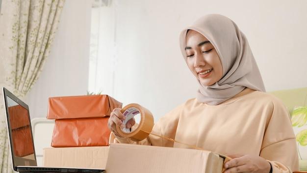 Schöner junger asiatischer geschäftsmann, der glücklich kundenaufträge verpackt