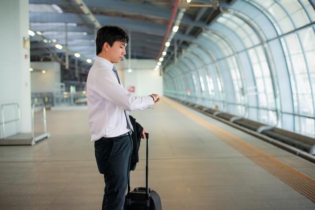 Schöner junger asiatischer geschäftsmannreisender, der in der hand uhr mit gepäck, wartezug bahnstation, reise und ferien betrachtet.
