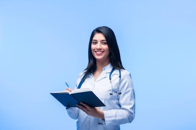 Schöner junger asiatischer mädchendoktor, mit einem notizbuch für aufzeichnungen lokalisiert auf einem blauen hintergrund. medizinstudent für allgemeinmedizin. das konzept der medizinischen ausbildung in indien