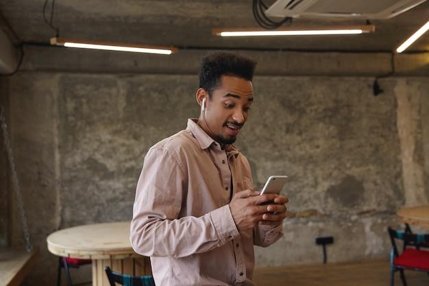 Schöner junger bärtiger mann mit offenen augen und dunkler haut, der über dem innenraum des stadtcafés mit smartphone in erhobenen händen steht, gute nachrichten liest und angenehm überrascht ist