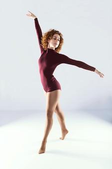 Schöner junger berufstänzer, der über weißen hintergrund tanzt.